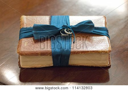 Bible with wedding bands tied with a teal ribbon