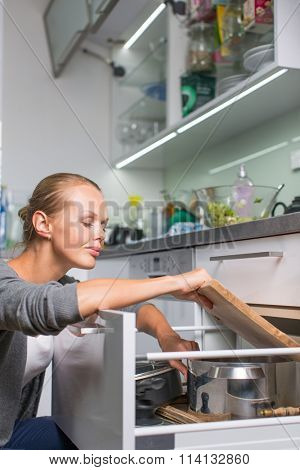 Young woman washing dishes in her modern kitchen, using a dishwasher, putting the dishes in their place