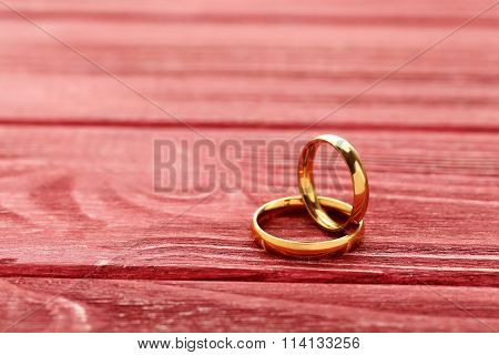 Golden Wedding Rings On A Red Wooden Table