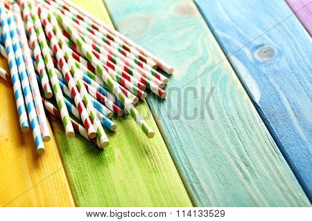 Striped Drink Straws On A Colorful Wooden Background