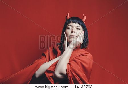 Pretty brunette woman with the red devil horns.