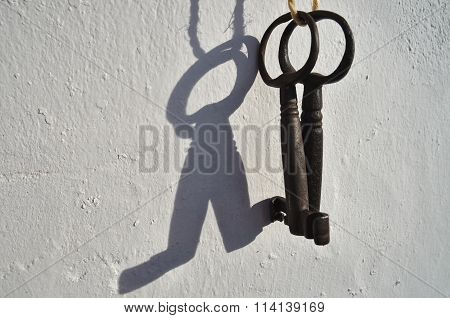 Two antique skeleton keys hanging from a white wall