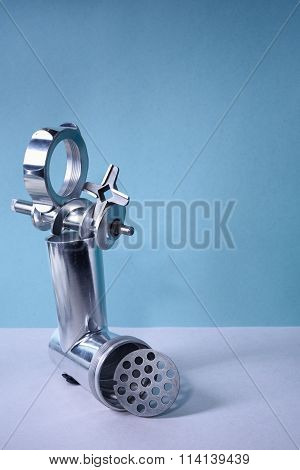 Kitchen utensil, steel meat grinder components, blue background. Free copy space.