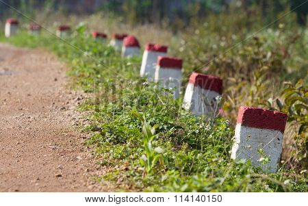 Red and white painted milestones in range on a country road