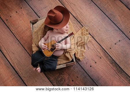Newborn Baby Cowboy Playing A Tiny Guitar
