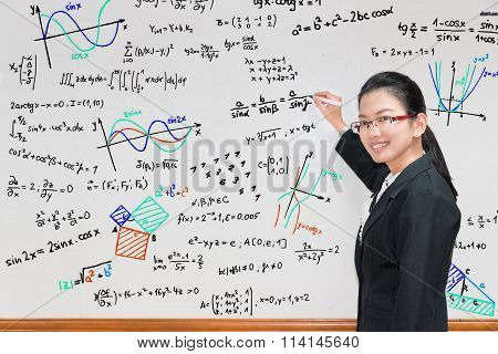 Asian Teacher Writing Various High School Maths Formula On Whiteboard