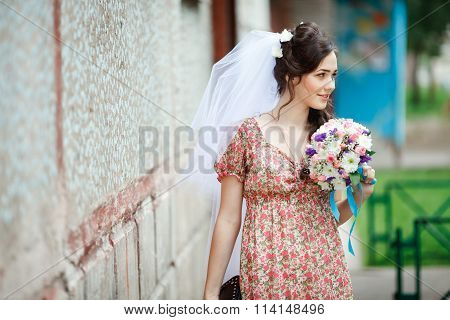 The bride in simple retro dress with floral pattern, already wearing veil, wedding bouquet and handb