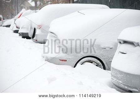 cars buried under snow after blizzard in residential area