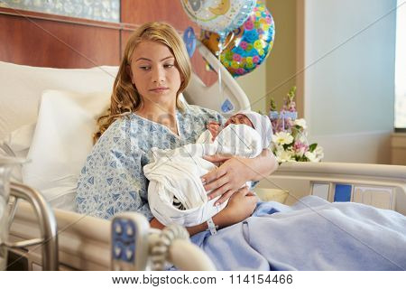 Unhappy Teenage Girl Holding Newborn Baby Son In Hospital