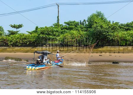 HO CHI MINH, VIETNAM - JAN 11, 2016: Local fishermans people fish in the Mekong river. Is located in the South of Vietnam, is the country's largest city, population 8 million.