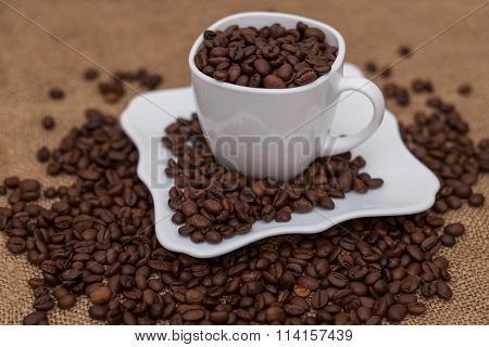 a scattering of coffee beans white cup and saucer
