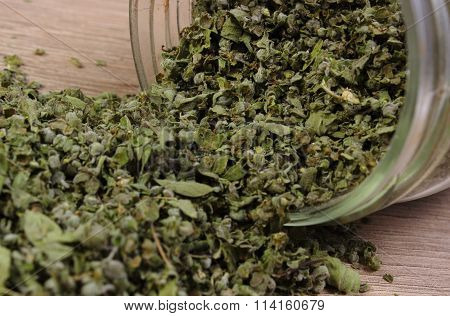 Dried Marjoram Spilling Out Of Glass Jar. Wooden Background