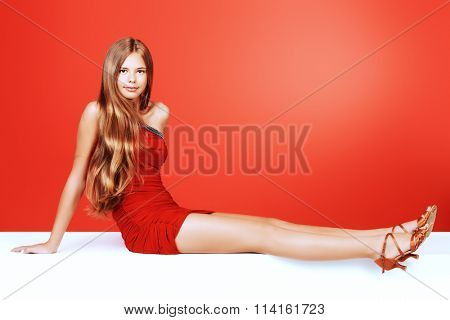 Beautiful girl in a red evening dress. Beauty, fashion. Full length portrait.