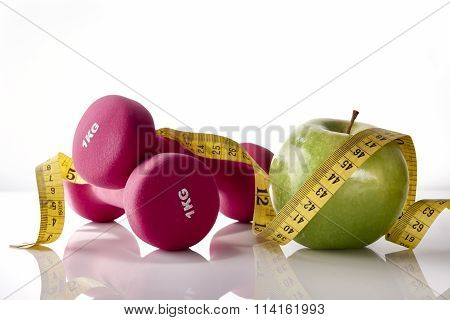 Apple Dumbbells And Tape Measure On White Glass Table Front