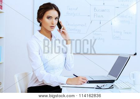 Elegant businesswoman talking on the phone at the office. Negotiations. Business, finance.