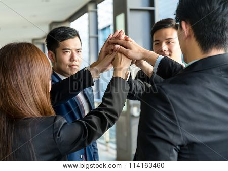 Group of business people joining hand together and raised up