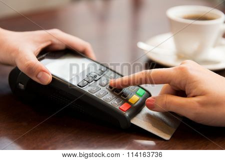close up of hands with credit card reader at cafe