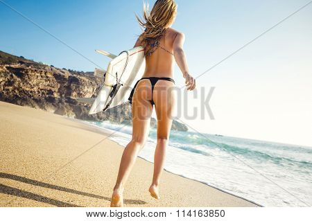 Beauitful young surfer girl running to the waves with her surfboard