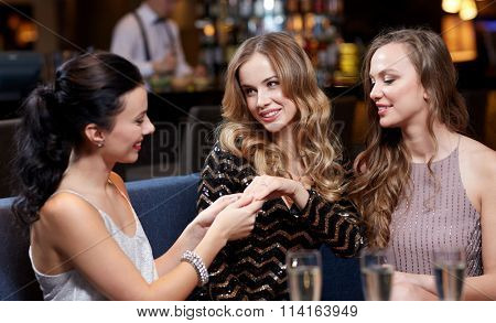 woman showing engagement ring to her friends