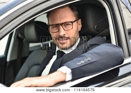 Portrait of smiling taxi driver in fancy car