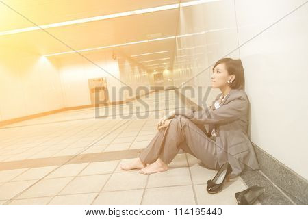 Asian young business woman take off her shoes and relax sitting on ground in modern building.