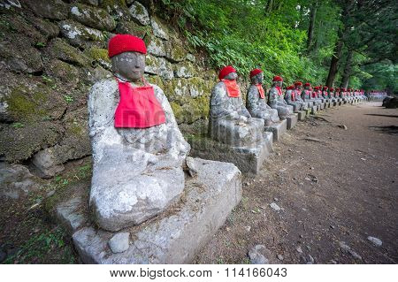 Perspective view, moss covered statues of Jizo in Nikko