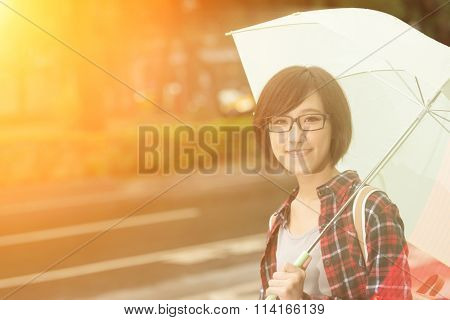 Young girl hold umbrella and stand at street in Taipei, Taiwan.