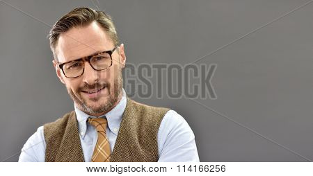 Mature man with eyeglasses standing on grey background