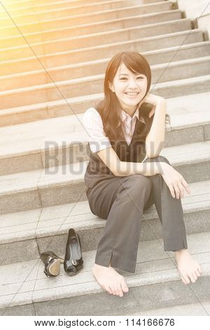 Happy smile business woman rest and take off her shoe in outside of urban.