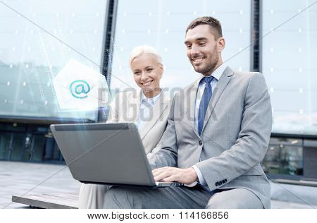 smiling businesspeople with laptop sending e-mail