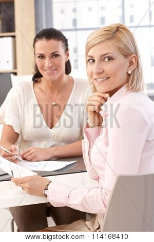 Close up of blonde casual, smiling female worker at business office, looking at camera.