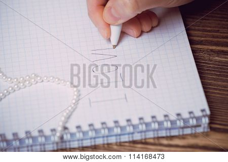 Closeup image of love letter written in copybook and human hand with a pen, over wooden background
