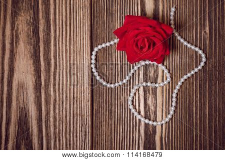 Red elegant rose and white pearl necklace over dark wooden background. Decoration for St.Valentines Day