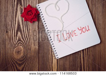 Love letter written in copybook over wooden background