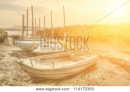 Abandoned boats in port in sunset city.