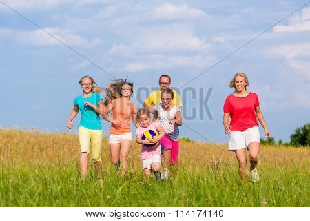 Family playing ball games on meadow running and having fun