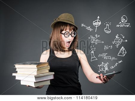 Education school and technology concept. Surprised nerd student with old books in one hand and e-rea
