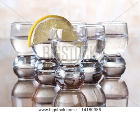Glass cup with tequila and lemon on table