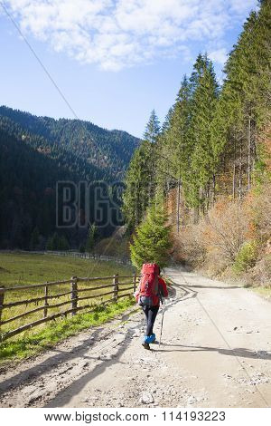 Girl With A Backpack Walking Along The Road.