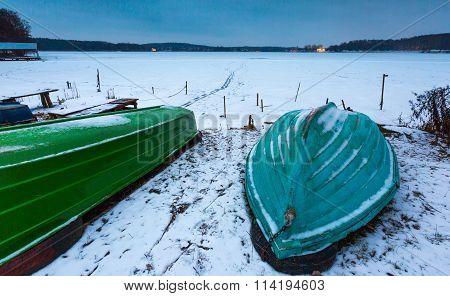 Fisherman Boats On Frozen Lake Shore. Winter Landscape