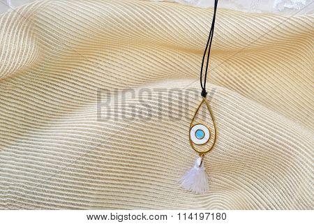 still life of a blue evil eye necklace