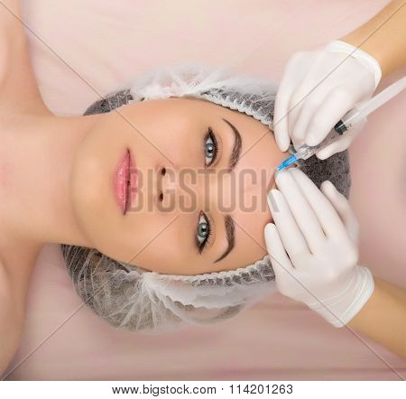 Beautician examining the face of a young female client at spa salon. beautician beauty injections. P