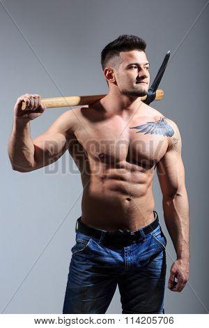 Muscular man holding pickaxe