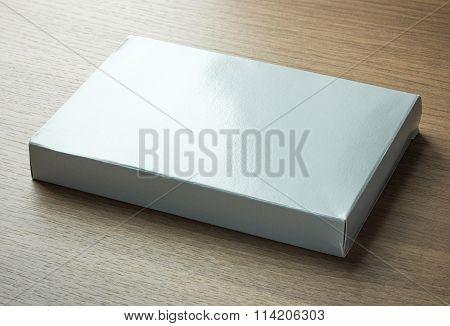 Blank Gray Paper Box On Dark Wood Background