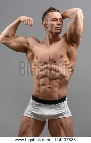 Shittless athletic man looking at the side and posing over grey background in white underwear