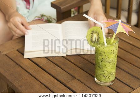 Glass of kiwi smoothie and a hands on opened book