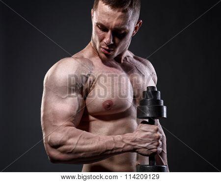 Athlete muscular bodybuilder training with dumbbell over dark background