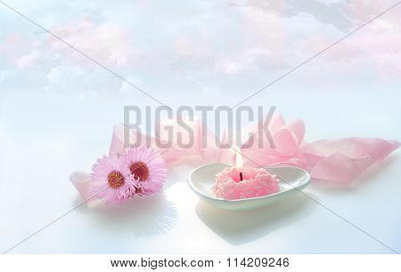 pink heart shaped burn candle with pink ribbon and flowers on blue sky background