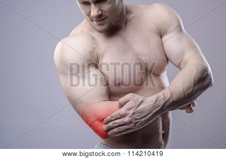 Athletic muscular man has pain in the elbow. Red spot of injury