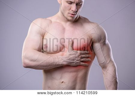 Athletic muscular man has pain in the heart. Red spot of injury